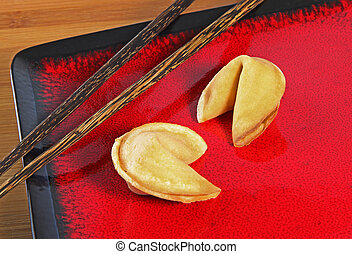 Fortune Cookies - Two fortune cookies on a red plate with...