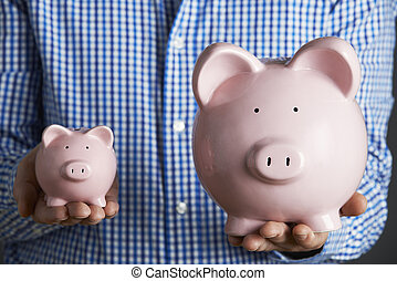 Man Holding Large And Small Piggy Bank