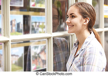 Smiling Young Woman Looking In Window Of Estate Agents
