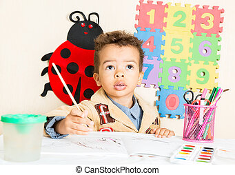 African American black boy drawing with colorful pencils in...