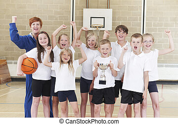 School Basketball Tean And Coach Celebrating Victory With...