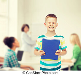 smiling little student boy with blue book - education,...