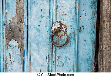 Old run-down blue painted wooden door nails - Closeup of...