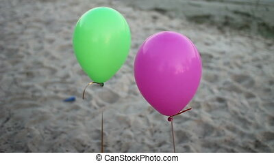 two colored balloons - colored balloons on sandy beach