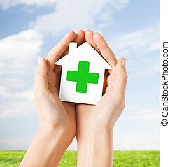 hands holding paper house with green cross