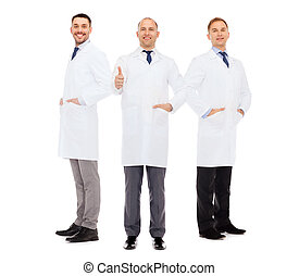 smiling male doctors in white coats - healthcare, profession...