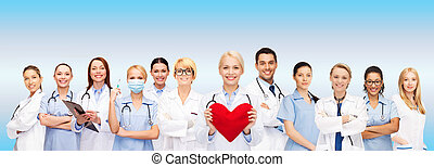 smiling doctors and nurses with red heart - healthcare and...