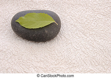StillLife-23-0008 - Basalt pebble with leaf on a white towel