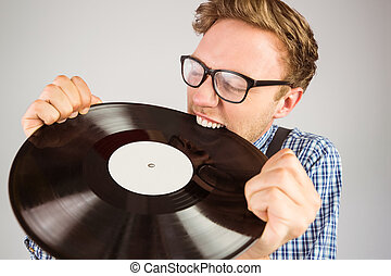 Geeky hipster biting vinyl record on grey background