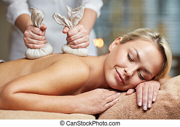 close up of woman lying on massage table in spa - people,...