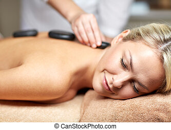 close up of woman having hot stone massage in spa - people,...