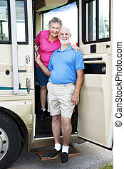 Senior Travelers in RV - Senior couple posing in the door of...