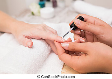 Nail technician giving customer a manicure at the beauty...