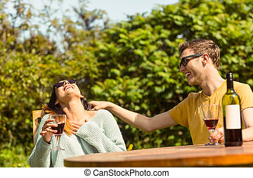 Young couple enjoying red wine outside in the garden