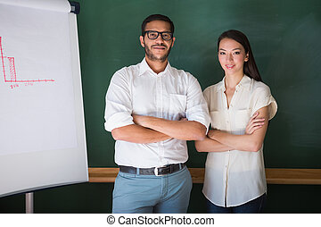 Two confident business people with arms crossed in office