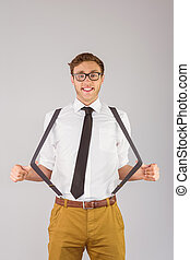 Geeky businessman pulling his suspenders on grey background