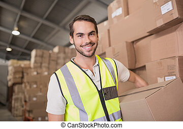 Worker carrying box in warehouse - Portrait of worker...