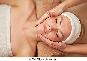 close up of young woman having face massage in spa - people,...