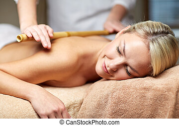 close up of woman lying and having massage in spa - people,...