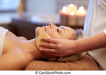 close up of woman having face massage in spa - people,...