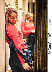 girl in the fitting shop trying on clothes in front of a...