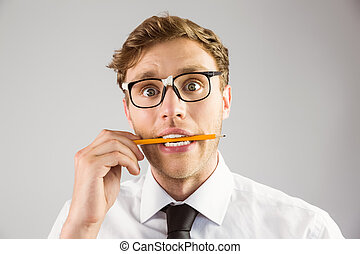 Geeky businessman biting a pencil on grey background