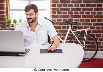 Casual designer using graphics tablet and laptop