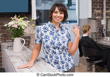 Confident hairdresser smiling at camera at the hair salon