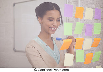 Smiling businesswoman writing on sticky notes on window in...