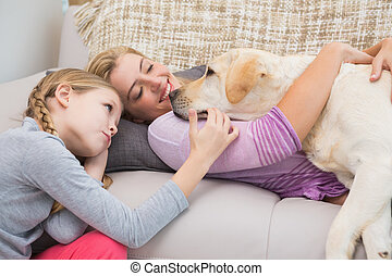 Mother and daughter with pet labrador at home in the living...