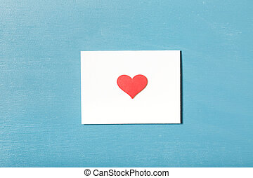 Card with hand crafted red heart on light blue wood...