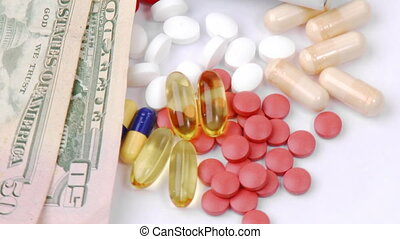 Dollars and colourful pills turning against white background