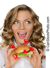 Woman with hamburger from hearts looking away