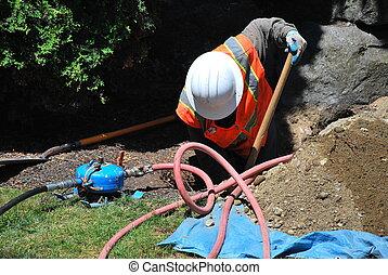 Utility Worker - Utility worker repairing a broken water...