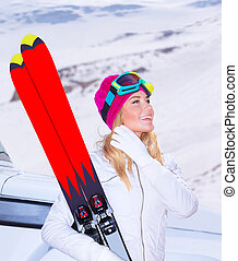 Enjoying ski sport - Happy woman holding in hands ski and...