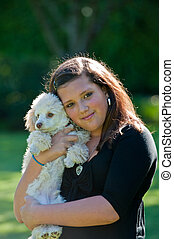 Girl and her dog - A teenage girl holding her poodle dog