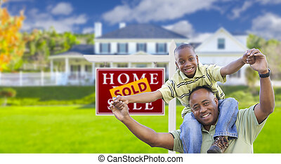 Father and Son In Front of Real Estate Sign and Home - Happy...