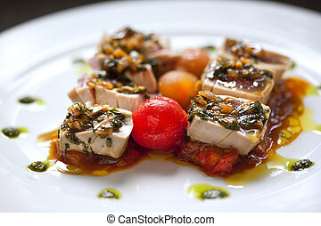 Seared tuna, tomato and sauce on a plate