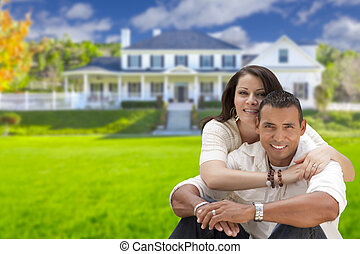 Happy Hispanic Young Couple in Front of Their New Home -...