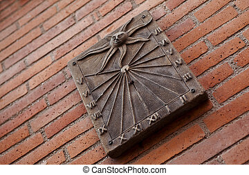 Sundial on a brick wall