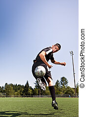 Hispanic soccer or football player kicking a ball - A shot...