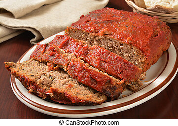Meatloaf - A serving platter with sliced meatloaf covered in...