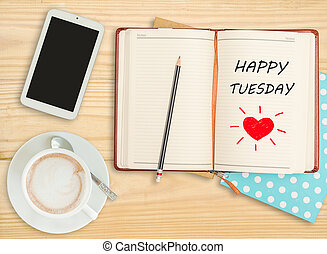 """Happy Tuesday""on notebook with smart phone and coffee cup"