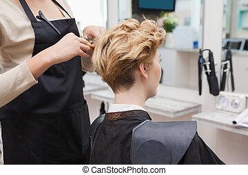 Happy hairdresser cutting