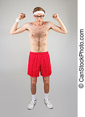 Geeky shirtless hipster flexing biceps on grey background