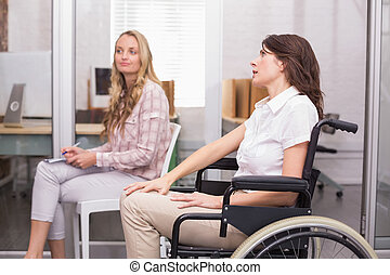 Businesswoman in wheelchair listening to presentation in the...