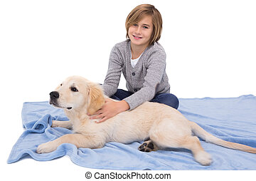 Child rubbing his dog lying on a blanket on white background