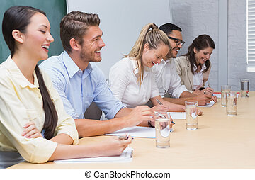 Smiling business people taking notes at a presentation in...
