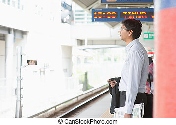 Indian businessman waiting train - Candid Asian Indian...