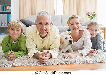 Happy parents with their children and puppy on floor at home...